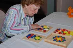 Gifts for Alzheimer's and dementia | An older woman enjoying a puzzle from Best Alzheimer's Products store