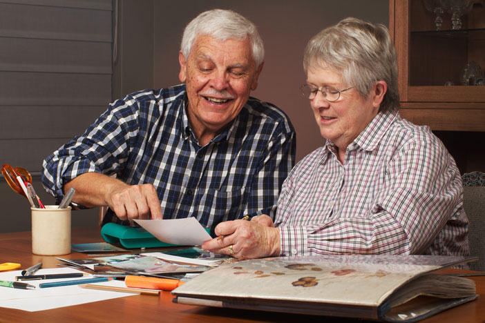 Older couple creating a memory book for Alzheimer's