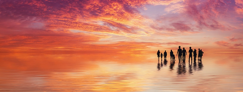 Hope on the Horizon - A group of people on a beach walking toward the sunset signifying a ray of hope in the quest for the cure for Alzheimer's