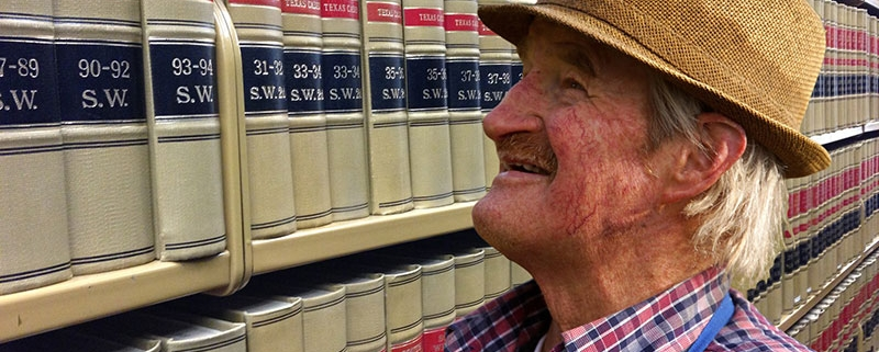 Make libraries dementia friendly. An older man looking at law books in a library.