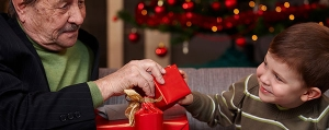 Alzheimer's Gift Guide - a little boy giving his grandfather a Christmas gift.